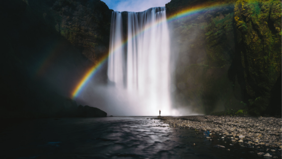 Rainbow being cast over rushing waterfall